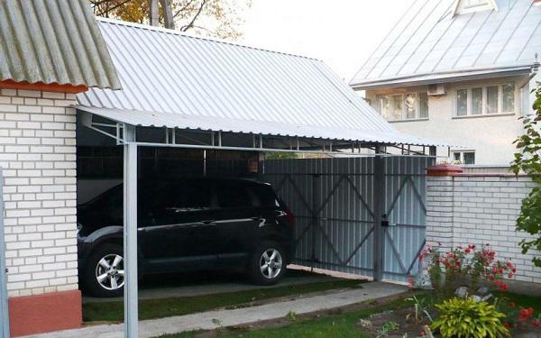 Крытая стоянка для автомобиля или полноценный гараж может иметь ворота, встроенные в забор, проходящий вдоль красной линии участка. Такой вариант пристройки не только удобен, но и практичен