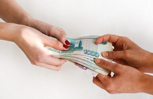 Мужчина передает женщине деньги в счет оплаты алиментов