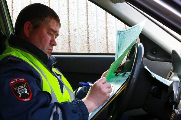 Сотрудник ГИБДД выписывает штраф водителю