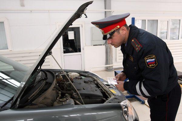 Сотрудник ГИБДД осматривает машину